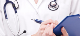 Doctor completing on medical card. Isolated on a white.